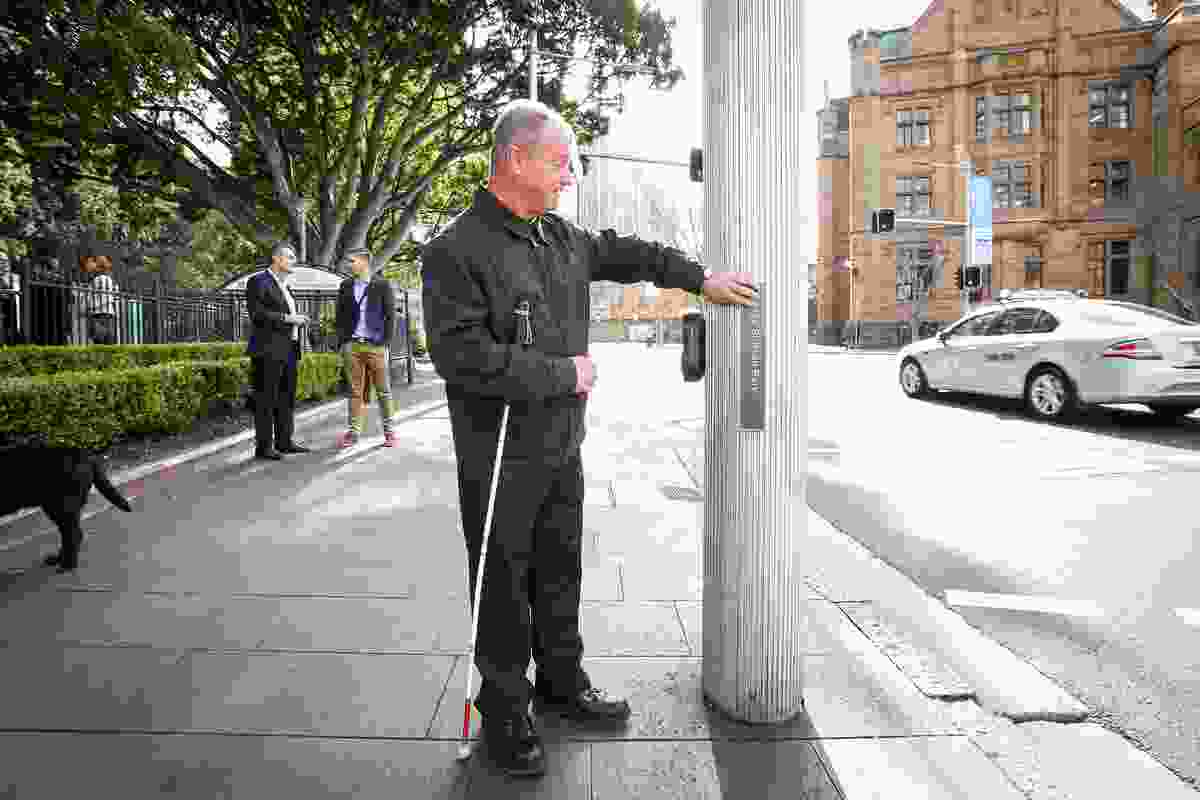 A man uses a tactile sign in Sydney.