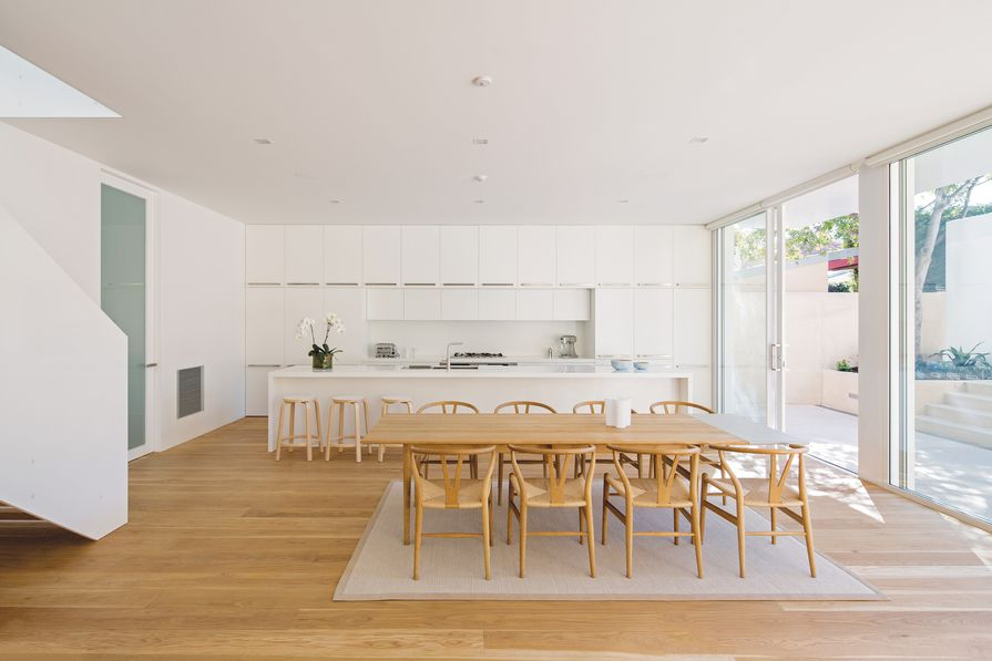 The new living area includes a large kitchen in a crisp, white palette that continues throughout the house.