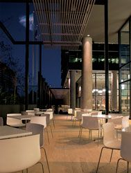 Outdoor cafe, looking towards the courtyard. The outdoor spaces are designed as an extension of the indoor communal facilities. The horizontal sunscreens protect the podium facades from solar heat gain and define the cafe seating area.