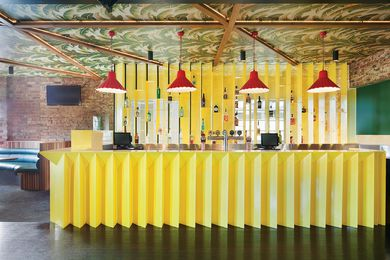 Beneath banana plant print wallpaper, another upstairs bar has painted steel Barfront and joinery detailing.