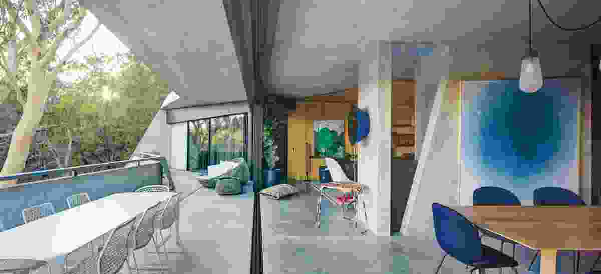 The living areas of the residence are arranged on the upper level, where a wide concrete eave shades an expansive balcony. Artwork: Sally Ross.