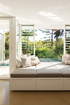 The living spaces at the back of the house open up to the pool and catch glimpses of the bay beyond.
