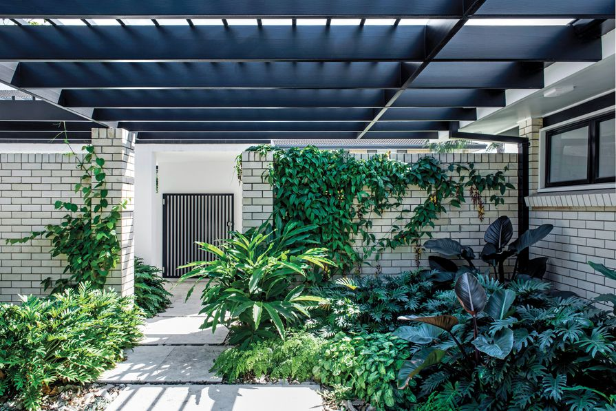 The entry courtyard is a mix of shades of grey and green that highlights various foliage textures, with a ground layer of travertine pavers over sandstone river pebbles.