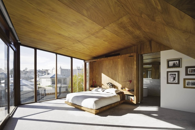The main bedroom's timber-lined ceiling follows the external roof form.