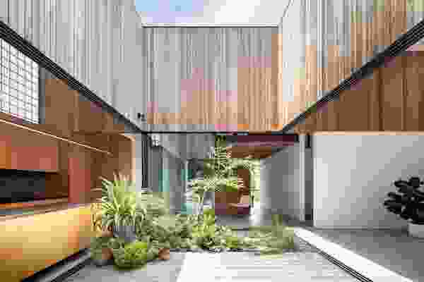 The central courtyard, lined with a landscaped garden, frames the sky and forms a pivot point around which daily life revolves.