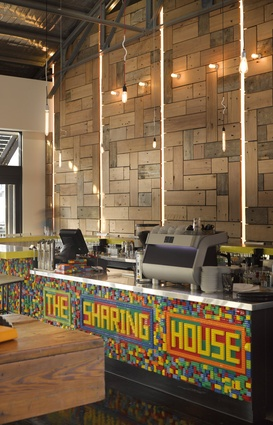 The Sharing House: A lego-clad bar contrasts with wharf timber on the wall behind.