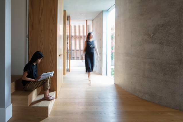 A curved concrete wall gives the entry a sense of drama, gradually revealing the new living areas.