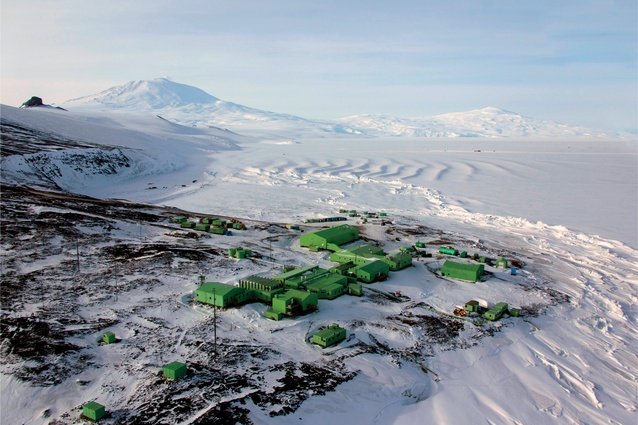 Scott Base with Mount Erebus in the background. There were differing accounts about why the buildings were painted green. A popular theory was that the Superintendent, Bob Thomson, liked Ireland's white cottages surrounded by green and reversed this combination for Scott Base.