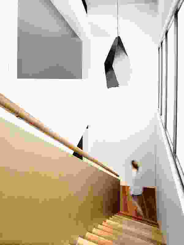 An elegantly minimal pendant light from Melbourne designer Edward Linacre hangs in the stairwell.