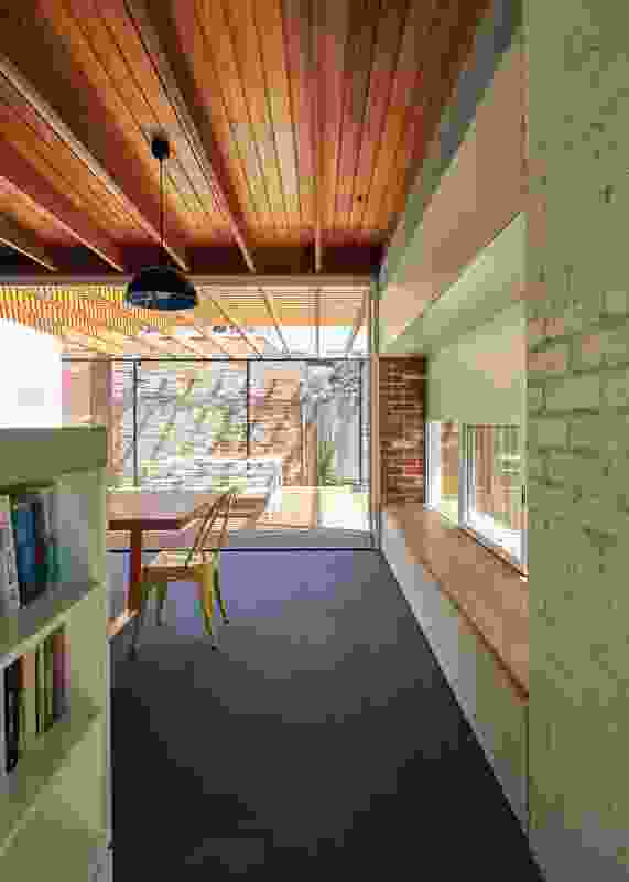 Expressed ceiling beams and timber battens extend from the interior onto the adjacent decks.