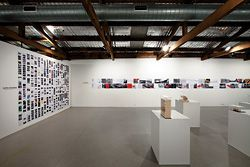Installation view, with Marcus Trimble's blog Super Colossal on the left. The back wall shows Choi Ropiha's Ballast Point Park, Sydney, and the TKTS booth in New York. Photography Murray Fredericks, courtesy of Boutwell Draper Gallery, Sydney.