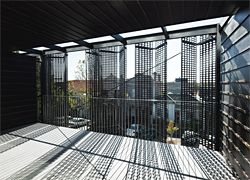 Folding pressed aluminium screens shield the balconies and windows of the north-facing facade. Image: Peter Bennetts
