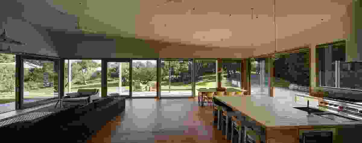 The renovation opened up the kitchen and  dining area to adjoining gardens through floor-to-ceiling, high-performance glazing.